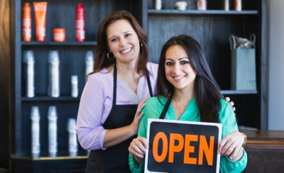 Shopkeepers-with-open-sign-900x550